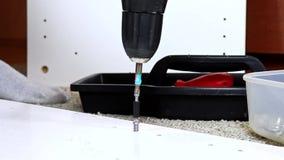 Mobilia di montaggio dal truciolato, facendo uso di un cacciavite senza cordone, fine su stock footage
