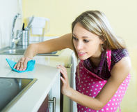 Mobilia di pulizia della domestica in cucina Immagini Stock
