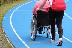 Mobiliteitsrolstoel op het atletische spoor tijdens sportief e stock foto's