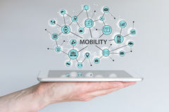 Mobility concept. Male hand holding modern smart phone or tablet with illustration Stock Images