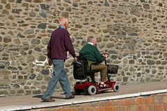 Mobility for the Disabled. Disabled elderly man riding a mobility vehicle on an uphill path, with another elderly man walking behind Stock Image