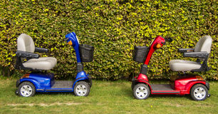 Mobility scooters. A red and blue mobility scooters on the grass stock images
