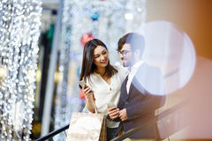 Mobility. Woman with smartphone carrying paperbags and talking to businessman on escalator in the mall Royalty Free Stock Images