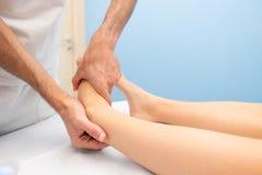 Mobilização do tornozelo de um fisioterapeuta imagens de stock