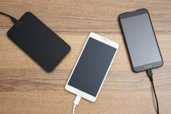 Mobilni mądrze telefony ładuje na drewnianym biurku Zdjęcie Stock