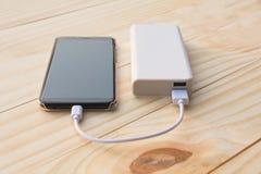 Mobilni mądrze telefony ładuje z władzą deponują pieniądze na biurku i kopii sp fotografia stock