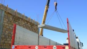 Mobilny żuraw podnosi betonową płytę obok niedokończonego budynku zbiory