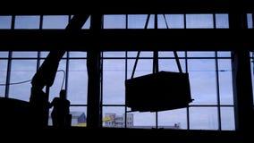 Mobilny żuraw podnosi zbiornika z materiałami budowlanymi Pracownik monitoruje pozycję ładunek zbiory