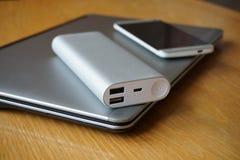 Mobilny biuro z aluminiowym laptopem, telefonem komórkowym i źródłem zasilania na drewnianym stole, (władza bank) Fotografia Stock