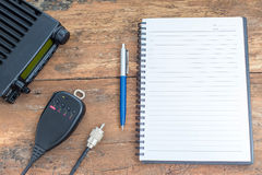 Mobilny radiowy transceiver i notatnik na drewno stole Obraz Stock