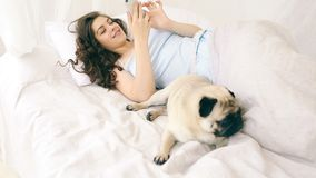 Mobilr phone user woman in bed with her funny small pug dog. Video footage. Weekend relaxed moment stock video