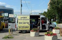 Mobilt kontor av bilförsäkring nära byggnaden för trafikpolisen Arkivbild
