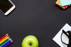 Mobiltelefon, äpple och brevpapper på skrivbordet Royaltyfri Fotografi