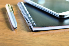 Mobiltelefon, anteckningsbok och penna på lackat trä Arkivbilder