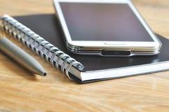 Mobiltelefon, anteckningsbok och penna på lantligt trä Royaltyfria Foton