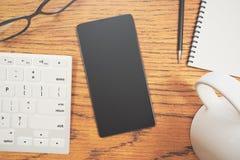 Mobiltelefon auf Schreibtischnahaufnahme Lizenzfreie Stockfotografie