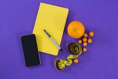 Mobiltelefon bok, penna och att mäta bandet och citrusfrukt Arkivbilder