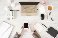 Mobiltelefon in der Hand auf dem Arbeitsplatz Lizenzfreie Stockbilder