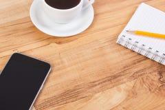 Mobiltelefon eller smartphone med notepaden för att skriva anmärkningar och koppen kaffe, kopieringsutrymme för text ombord Arkivfoton