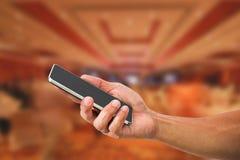 Mobiltelefon för hand för man` s hållande på suddig hotelllobby Royaltyfri Bild