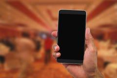 Mobiltelefon för hand för man` s hållande på suddig hotelllobby Arkivbild