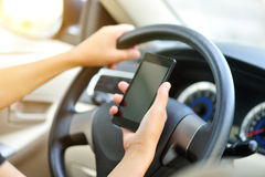 Mobiltelefon för kvinnachaufförbruk som kör bilen Royaltyfri Fotografi
