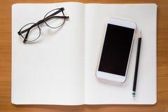 Mobiltelefon, glasögon och blyertspenna på den vita anteckningsboken Arkivfoton