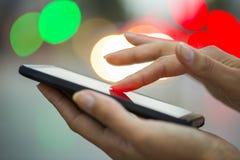 Mobiltelefon i en kvinnas hand, stad av ljus bakgrund Arkivbild