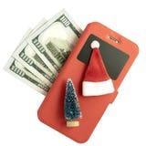 Mobiltelefon i ett rött fall, en souvenirjulgran och en Santa Claus hatt och trehundra US dollar på en vit bakgrund fotografering för bildbyråer