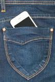 Mobiltelefon i fick- jeans Arkivfoton
