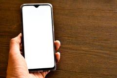 Mobiltelefon i hand på trätabellen med kopieringsutrymme royaltyfria foton