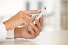 Mobiltelefon i isolerade en kvinnas hand Royaltyfri Fotografi