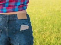 Mobiltelefon i utomhus- fick- jean av flickan Royaltyfria Bilder