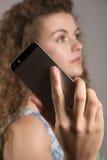 Mobiltelefon med användaren i mjuk fokus Royaltyfri Foto