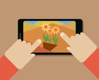 Mobiltelefon med bilden av blommor och händer Fotografering för Bildbyråer