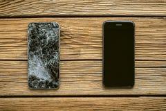 Mobiltelefon med den brutna pekskärmen på träbakgrund royaltyfria bilder