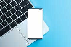 Mobiltelefon med den tomma skärmen på bärbara datorn på blå bakgrund framf?rande 3d royaltyfri bild