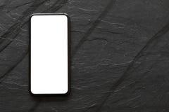 Mobiltelefon med den tomma skärmen på svart stenyttersida Royaltyfri Bild