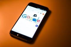 Mobiltelefon med det Google klottret som firar hålstansmaskin Fotografering för Bildbyråer