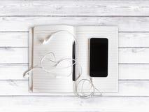 Mobiltelefon med hörlurar och den tomma dagboken med en penna på vit w Royaltyfria Foton