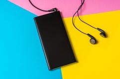 Mobiltelefon med hörlurar som isoleras på färgrik bakgrund fotografering för bildbyråer