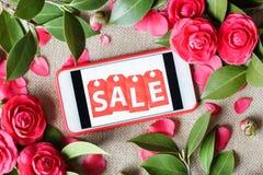 Mobiltelefon med inskriftförsäljning och rosa rosor Lekmanna- l?genhet, b?sta sikt royaltyfria foton