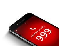 Mobiltelefon med nöd- nummer 999 över vit Arkivbilder