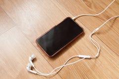 Mobiltelefon med vit hörlurar Fotografering för Bildbyråer