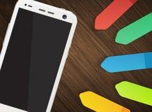 Mobiltelefon mit bunten Aufklebern auf hölzernem Hintergrund Stockfotos