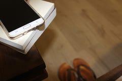 Mobiltelefon och böcker på nightstand på nattetid royaltyfria bilder