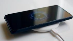 Mobiltelefon och en trådlös laddande apparat Tr?dl?st laddande begrepp lager videofilmer