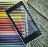 Mobiltelefon och färgpennor Arkivfoto