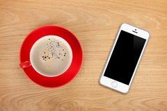 Mobiltelefon- och kaffekopp arkivbilder
