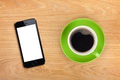 Mobiltelefon- och kaffekopp arkivfoton